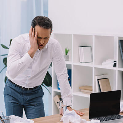 suffering businessman with painful migraine
