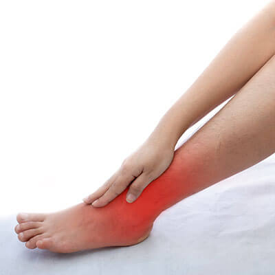 young woman with ankle pain at white background
